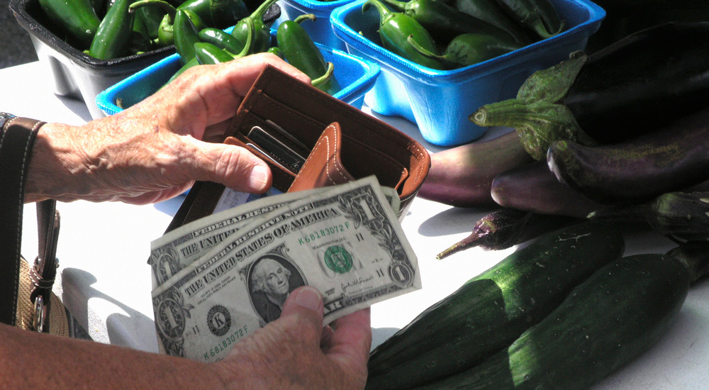 Woman Paying Cash for Fresh Vegetables