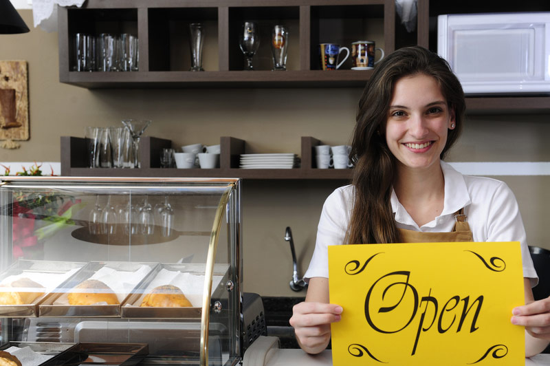 Woman Who Owns Bakery Holding Open Sign